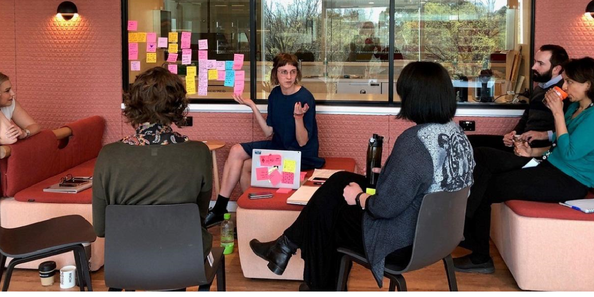 Image of people sitting around discussing content on post-it notes.